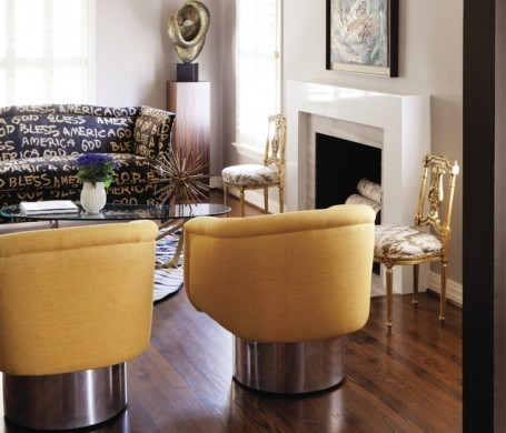 Sunny, midcentury swivel chairs and a minimal, custom mantlepiece give this Dallas room the clean lines needed to contrast a pair of dramatic, gilt chairs.