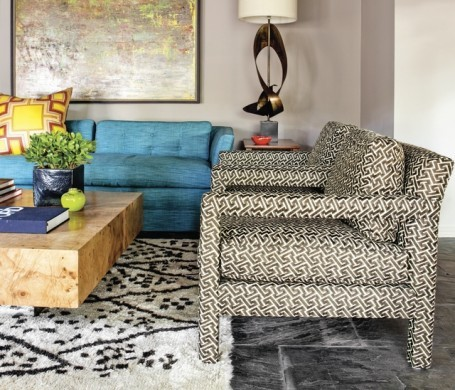 A substantial Milo Baughman coffee table, geometric chairs in fabric by Lee Jofa, and patterned Moroccan rug add architectural interest in this Dallas home.